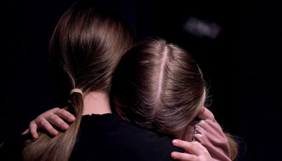 Mother hugging frightened little girl in dark room, victims of m