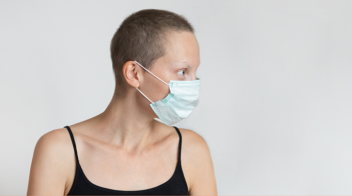 Profile side view of short haired young adult woman wearing protective facial mask on face against wall indoors. Coronavirus outbreak prevention. Vulnerable category person. Virus pandemic awareness